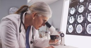 A female researcher with a silver ponytail looks through a microscope.