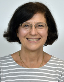Dr. Annamaria Vezzani smiling in front of a grey background.
