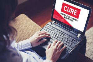 Woman sitting at a laptop participating in a CURE webinar.