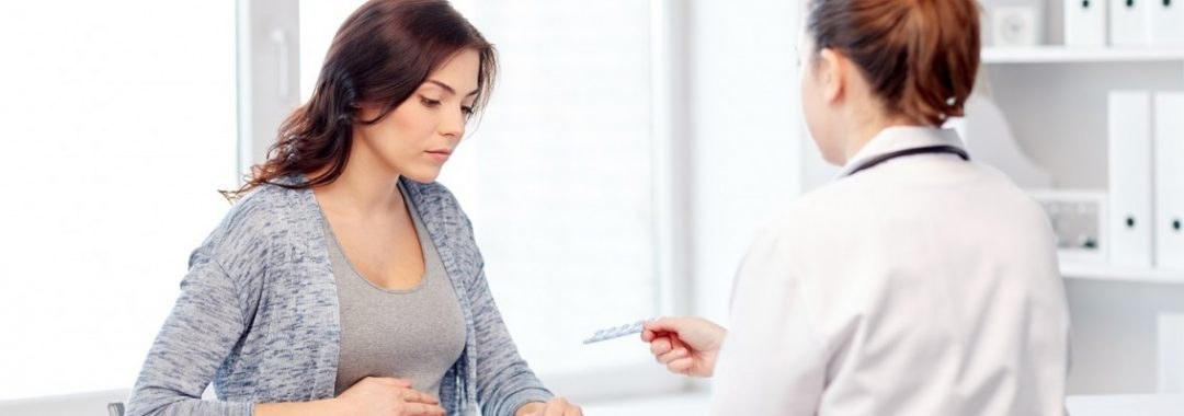 A visibly pregnant woman looks at a prescription, which her doctor is handing to her.