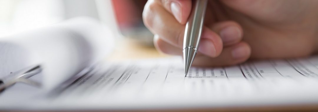 A close-up shot of a white person filling out a survey or forms with a silver pen.