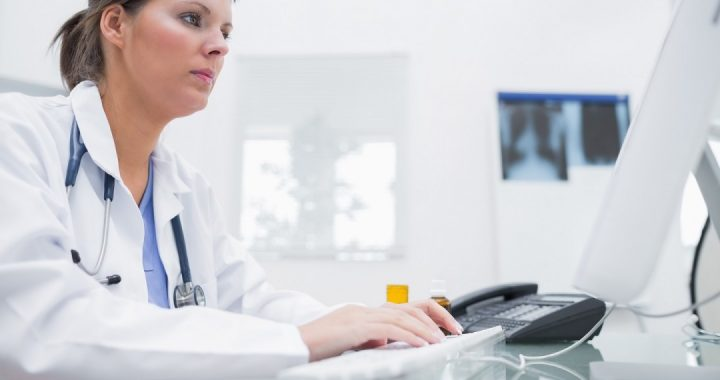 Doctor wearing a white coat typing at a computer