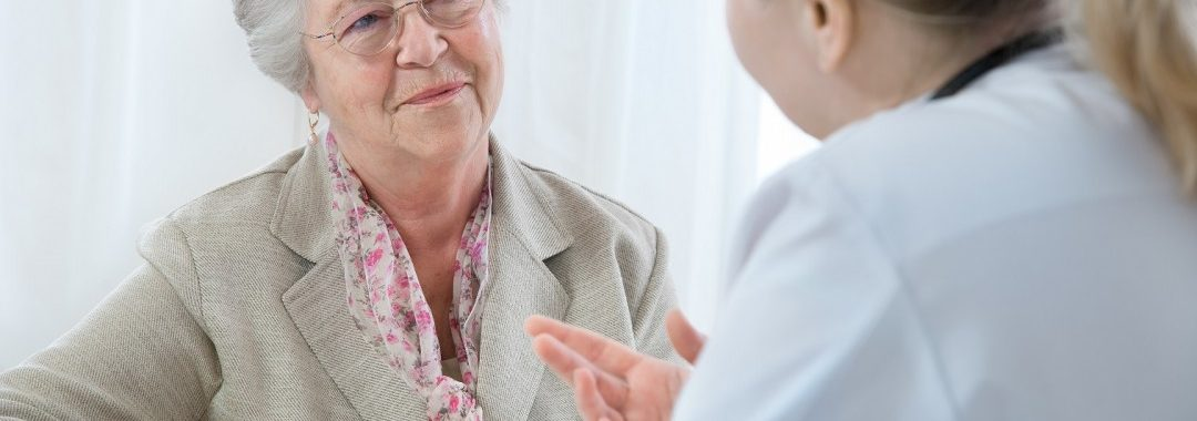 An elderly woman speaks with her doctor, who is explaining the prescription.