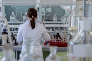 Woman standing in a research lab wearing a white coat with her back to the camera.