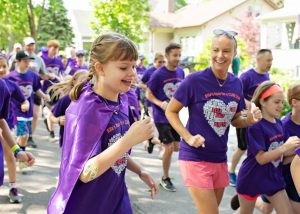 Ella and her mother running among friends all wearing purple shirts at Ella's Race in 2019