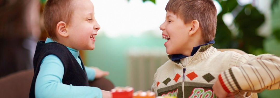Two children happy at a table together.