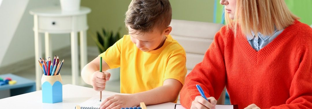 Female psychologist working with boy who has autism and epilepsy.