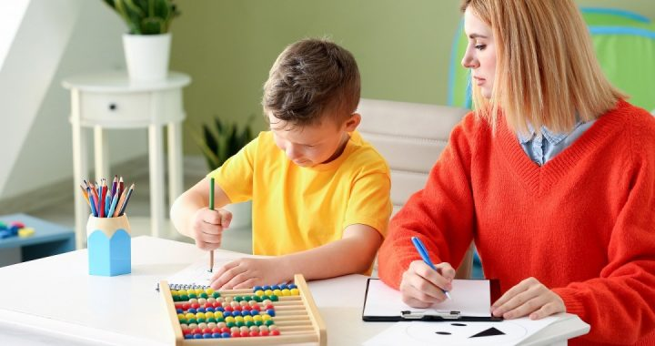 Female psychologist working with boy who has autism