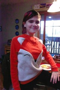 Yasya, standing in the kitchen wearing a fox costume.
