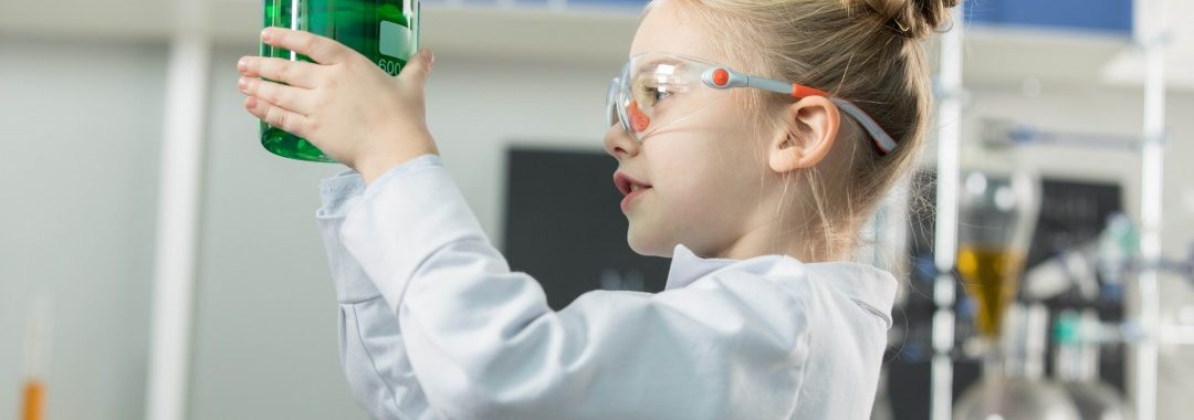 A little girl dressed in a white lab coat holding a beaker of cool green liquid.