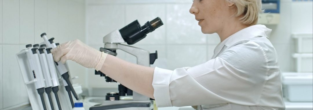 A blonde woman in a lab coat is conducting genetic research in the lab.