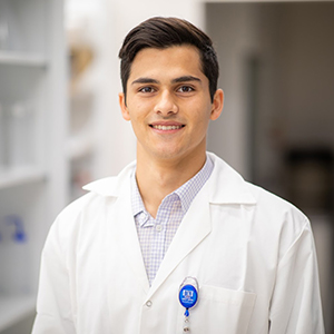 Nathan Bliss is dressed in a white lab coat standing in a research facility.