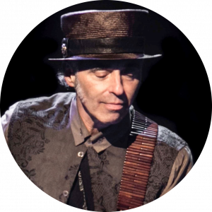 The legendary Nils Lofgren looks down toward his guitar while performing.