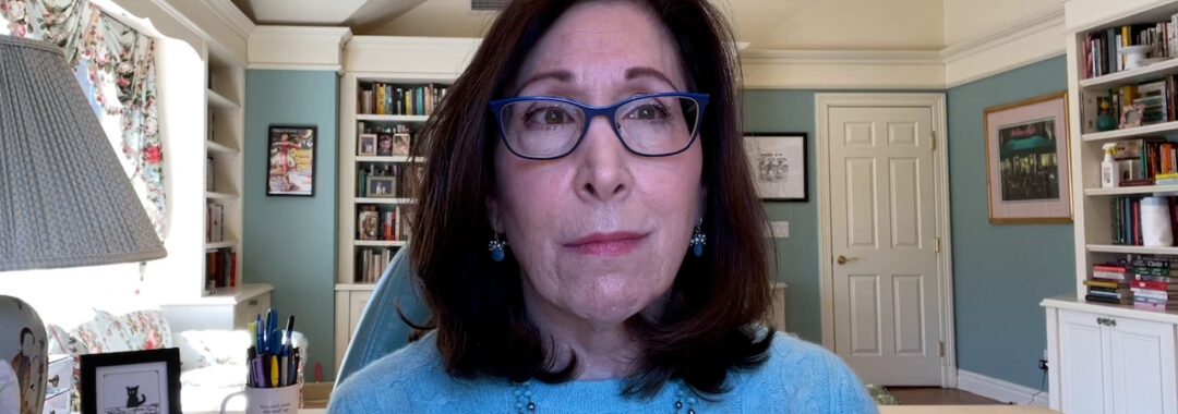 a woman with blue glasses, blue sweater, and a blue necklace talking