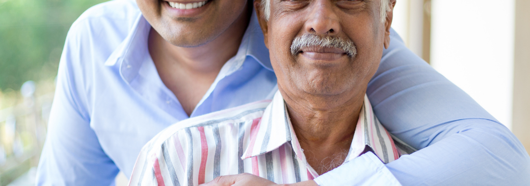 a younger man hugs his elderly father from behind as they smile at the camera